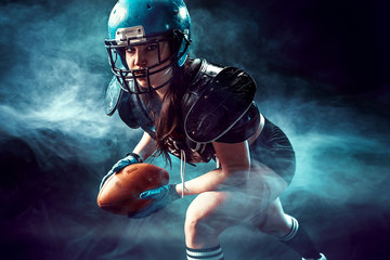 Sportive serious woman in helmet of rugby player holding ball in smoke.