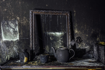Burnt room interior. Burnt still life. Charred wall, picture frame, pot with burned rose in black soot