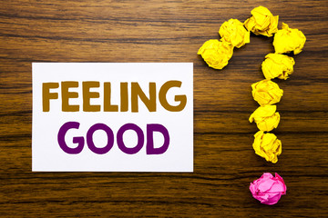 Handwritten text showing Feeling Good. Business concept for Happy Positive Attitude Written on sticky note paper, wooden background with question mark from sticky note. For asking questions.