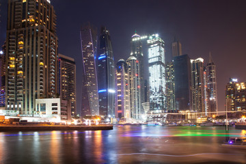 DUBAI, UAE - FEBRUARY 2018: Colorful evening on canal and promenade in Dubai Marina,Dubai,United Arab Emirates