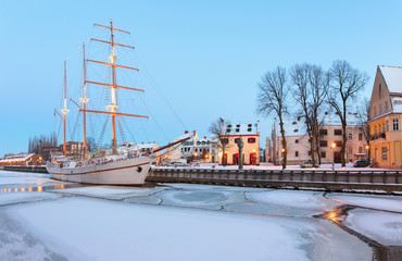 Ship-restaurant is docked on the Danes river quay. Early morning winter scene of Klaipeda old town district. Klaipeda, Lithuania.