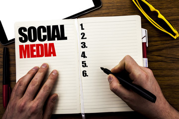 Word, writing Social Media. Business concept for Global Internet Network Written on book, wooden background with businessman hand, finger writing on the notebook.