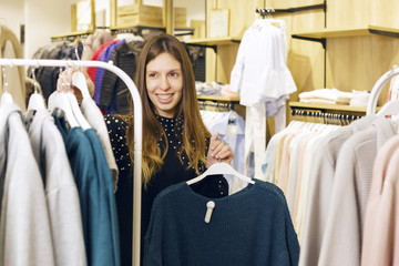 Girl working as a store assistant, sorting clothes on store's rails. Friendly.