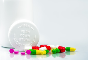 Colorful pills on white background and childproof bottle with blank label and copy space. Pharmacy department in the hospital concept. Drug store concept.
