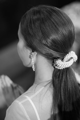 Back view of unrecognizable young woman with decorate hair in white wedding dress.