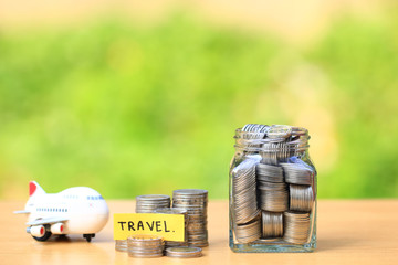 Saving planning for Travel budget of holiday concept,Financial,Stack of coins money in the glass bottle and airplane with natural green background