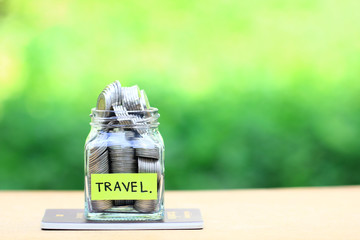 Saving planning for Travel budget of holiday concept,Financial,Stack of coins money in the glass bottle on passport with natural green background
