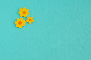 Three Wooden Yellow Craft Flowers on an Aqua Background.