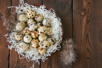 Fresh quail eggs in a plate on a wooden background. Rustic style. Top view and copy space.