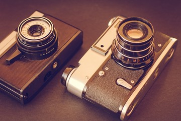 Old cameras on the table. Two vintage cameras on a black background.
