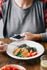 Healthy vegetarian food concept. Woman eating vegetarian food (black quinoa and cutlets from oatmeal and prunes)