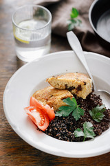 Close up plate with black quinoa and oatmeal cutlets with prunes on wooden table with glass water with lemon. Vegetarian dinner table