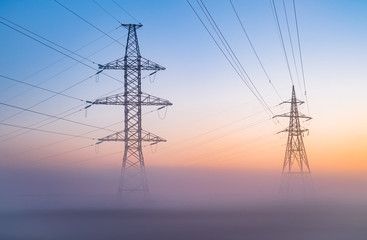 transmission towers in the fog at the background of the dawn sky. High Voltage power line silhouette during the sunset in a clear sky
