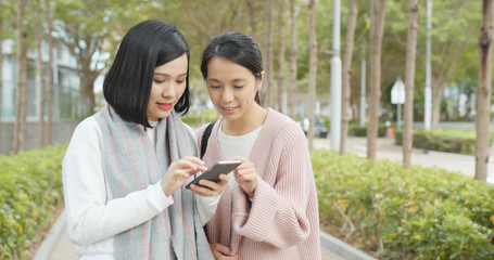 Friends finding location on cellphone at outdoor