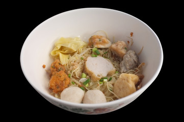 Thailand popular street food , Hakka Chinese noodle food consisting primarily of tofu. , Hakka noodles in a white bowl topping with pork ball fish ball shrimp ball fried wontons fried taro minced pork