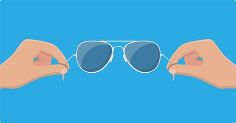 Aviator sunglasses in hand. Protective eyewear.