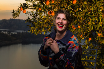 Young caucasian woman with short hair and flashy jacket poses under an orange tree at sunset
