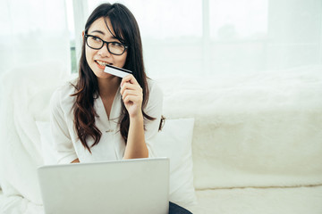 Young asian girl is freelancer with her private business at home office, working with laptop, coffee, online marketing. Young woman startup her SME business.