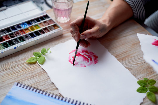 The process of creating an illustration by the artist. Watercolor paint. Hand with brush