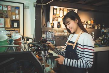 Beautiful asian barista using coffee maker machine in coffee shop