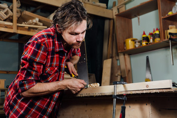 carpenter man's hand treats the tree, cuts the shavings.