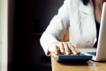 Asian business woman using calculator for accounting and analyzing investment in front of computer laptop at office workspace.  banking , savings , accountant , finances and economy concept.