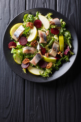 Smoked mackerel with apples, walnuts, beets and various lettuce close-up on a plate. Vertical top view