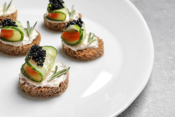 Tasty appetizer with black caviar and cucumber on plate