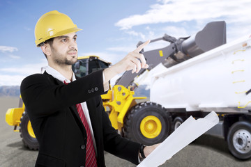 Male architect or contractor standing in front of an excavator loading truck with soil on a construction site