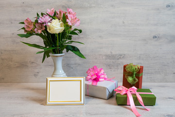 Colorful spring bouquet of rose, chrysanthemum and alstroemeria flowers in a vase with empty photoframe and gift boxes on wooden background