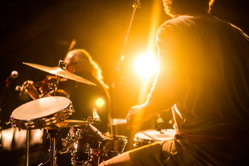 Drummer on stage playing with a band with gold yellow light shining in background  Fotomurales