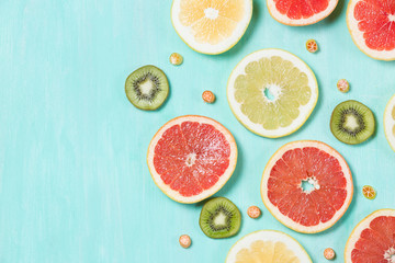 Above view on thin citrus chips: orange, lemon, grapefruit on turquoise wooden background. Vitamins