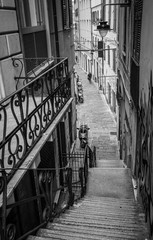 Black and White photo of Old narrow crowdless streets of the Old Genova district in Genoa, Italy.