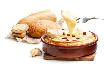 Delicious  hot baked camembert with sultanas isolated on white