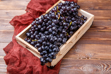 Image of black grapes in wooden box with claret cloth