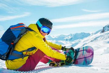 Image of sporty woman in helmet sitting on snow with snowboard