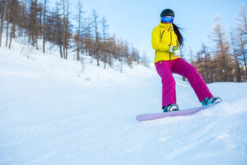 Image of athlete girl wearing helmet and mask snowboarding from snowy slope with trees