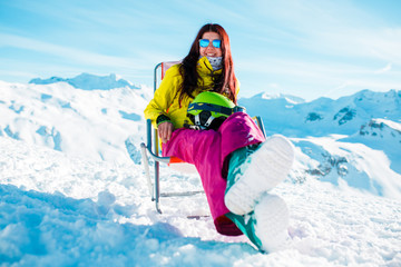 Image of sporty long-haired brunette with helmet resting on chair in winter resort