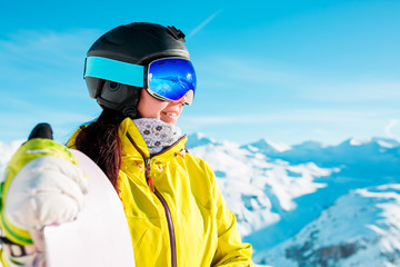 Image of smiling woman in helmet and mask with snowboard on background of snowy hills