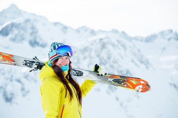 Image of sporty woman with skis on her shoulder in background of snowy hill
