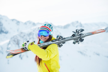Picture of woman in mask with skis on her shoulder standing sideways