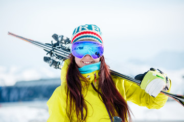 Photo of smiling sporty woman in mask with skis on her shoulder
