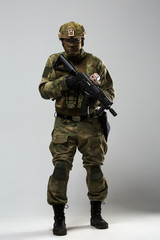 Full-length photo of military man in camouflage with gun