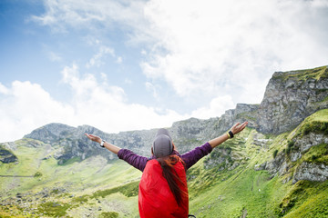 Image of woman with backpack against background of mountain landscape