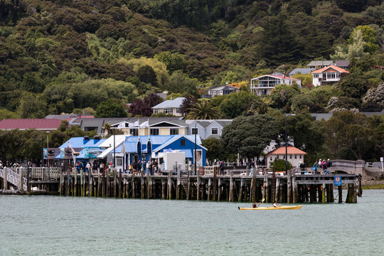 A view of Akaroa, New Zealand from the sea with cruise boat passengers enjoying the town
