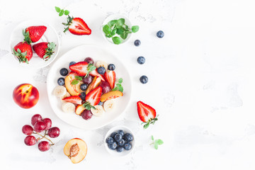 Fruit salad with strawberry, blueberry, peach, banana, grape and fresh fruits on white background. Flat lay, top view, copy space