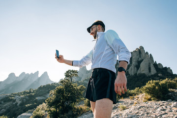 Trendy, fit and strong young man athlete in short running shorts and wind light jacket searches for network or connection on mobile smartphone, or makes photo selfie after workout or hike