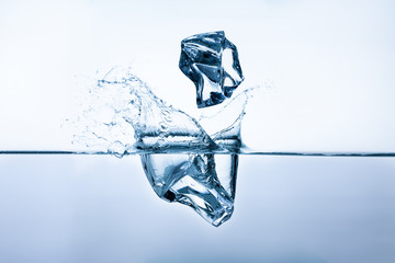 Ice cubes splashing into clear water