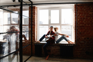 stylish young couple having fun in cozy bedroom in style loft,  feeling happy being together. The man plays the guitar and sings the song for the woman, sitting on a window sill.