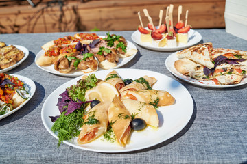 Delicious thin pancakes with salmon, dill and olives on white plate on dinner table outdoors, free space. Russian cuisine. Maslenitsa. Rolls of thin pancakes with smoked salmon